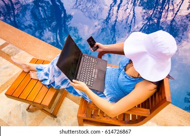Young woman in dress and white hat and using laptop and mobile phone computer sitting in a wooden lounger outdoor near swimming pool. Summer vacation day, freelance, working outdoor