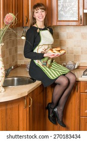young woman dressed in apron on the kitchen holding the plate full of pies