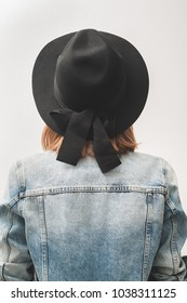 Young woman dressed black hat with bow and blue double denim jacket, Back view. White background.