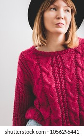 Young woman dressed black hat, knitted large viscous pink sweater. White background.