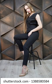 young woman dressed in black jumpsuit, sitting on a chair with high heels shoes posing in the studio. Beautiful blonde girl demonstrating stylish smart clothes against a wall on the background of volu
