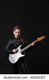 Young woman dressed in black leather clothes plays electric guitar
