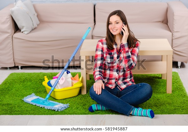 Young woman dressed in casual clothing, sitting on the floor and talking on the phone. Beside her detergents to clean the house. Rest after the successful cleaning house