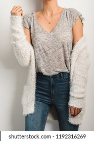 Young woman dressed gray t-shirt and fluffy knitted white cardigan.