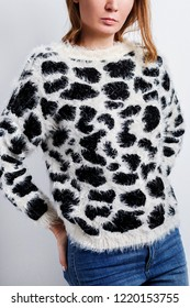 Young woman dressed knitted furry black and white sweater with leopard pattern and blue jeans.