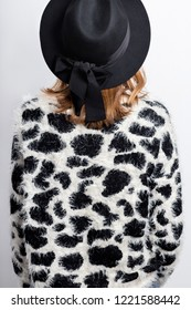 Young woman dressed knitted furry black and white sweater with leopard pattern and black hat. Back view.