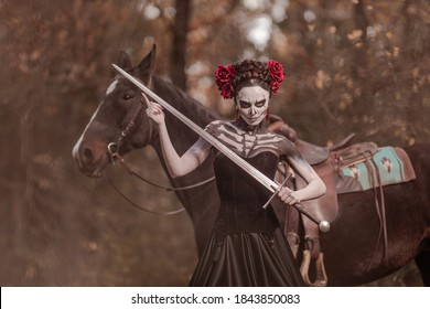 Young woman dressed as mexican symbol of day of the dead posing in forest with horse