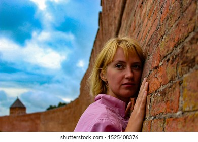 young woman dressed in a pink windbreaker leaned against the brick wall