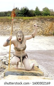 A young woman is  dressed as a prehistoric hunter.  She is covered with mud, filth and dirt and is seen in  a stone quarry surrounding.