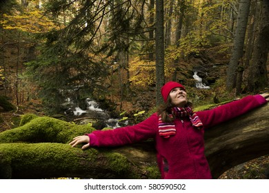 Young woman dressed in red, enjoying the colourful autumnal forest.
