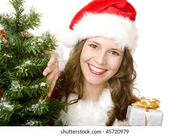 young woman dressed as Santa Claus is standing beside a fir tree, smiles happy and holds a Christmas gift in hand. Isolated on white.