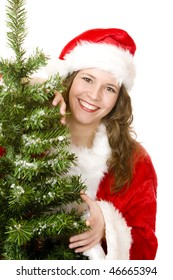 young woman dressed as Santa Claus is standing beside a Christmas tree and smiles happy. Isolated on white.