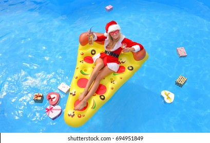 A young woman dressed in a Santa Claus suit lies in a pool on a sun bed. She has fun relaxing with drinks and sunshine watching her Christmas presents floating around her