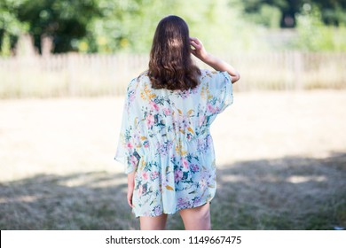 young woman dressed in summer clothes from behind