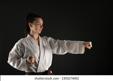 Young woman dressed in traditional kimono practicing her karate moves