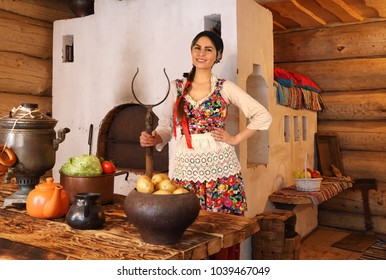 A young woman dressed in traditional Russian clothes stands at the table with vegetables in a typical Russian wooden log hut