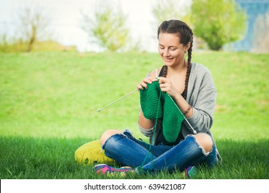 A young woman dressed in trendy jeans, a cardigan and with a backpack sitting in a city park on green grass and knitting a green sweater with knitting needles on a summer day