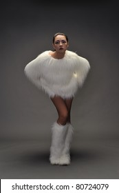 Young woman dressed in white fur coat and matching tall shoes leaning forward