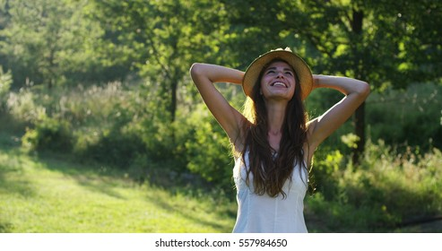 An young woman dressed in white with a straw hat smiles and enjoys a sunny day on a green woods background. Concept of freedom, liberty,lifestyle, equilibrium, connection to a nature and a green world
