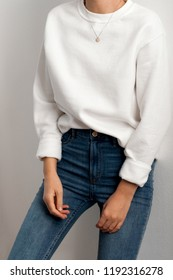 Young woman dressed white sweater and blue jeans.