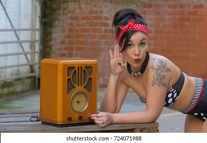 A young woman dresses up as a pin-up girl. She wears a black and white stripped vintage bathing suit. She over poses for the camera while listening to an old wooden  radio.