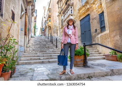 Young woman dressing elegantly in the historic stairs of Valetta in Malta