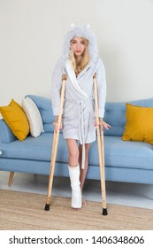 Young woman in a dressing gown with crutch and broken leg in cast in the room