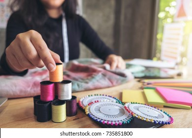 Young woman dressmaker or designer working as fashion designers, Choose yarns to the sewing fabric, profession and job occupation.