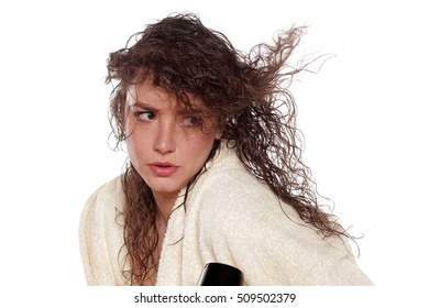 young woman dries her hair with a blow dryer