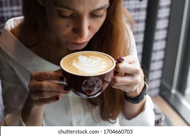 Young woman drinking cappuccino coffee near the window