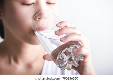 Young woman drinking clean water in her hand.