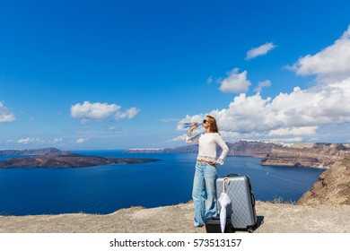 Young woman drinking clear water on the beach, Santorini island, Greece