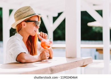 Young woman drinking cocktail in a beach bar