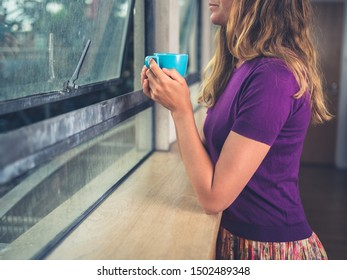 A young woman is drinking coffee by the window in a city apartment
