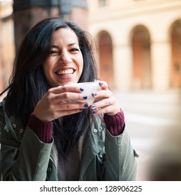 Young woman drinking coffee in a cafe outdoors. Shallow depth of field.