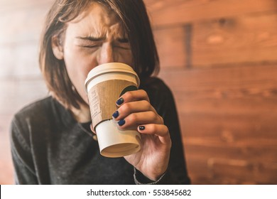 Young woman drinking a coffee at cafe and grimacing because the drink is too hot and burning her tongue. Beautiful caucasian girl with short hair, focus on the hand holding the mug.