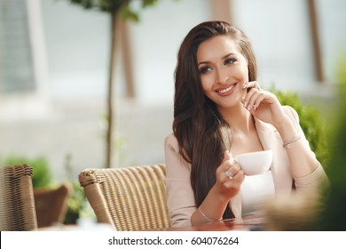 Young woman drinking coffee in a cafe outdoors.Image of happy female in open air cafe looking at camera in urban environment. A young woman sitting alone at breakfast table at resort