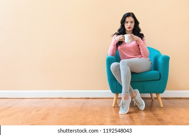 Young woman drinking coffee in a chair