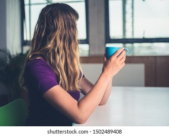 A young woman is drinking coffee in a city apartment