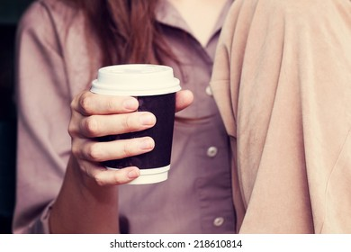 Young woman drinking coffee from am disposable cup