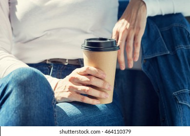 Young woman drinking coffee from disposable brown paper cup
