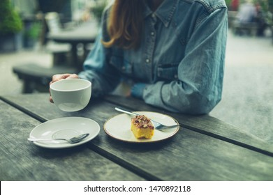 A young woman is drinking coffee and eating cake in nature
