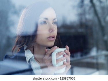 Young woman drinking coffee looking through the window