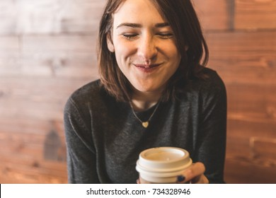 Young woman drinking a coffee and making funny and smiling face. Beautiful caucasian girl in a cafe in Toronto.