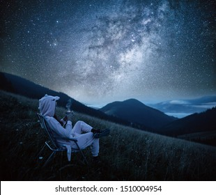 Young woman drinking coffee at mountains on the background of the milky way. Woman looking at beautiful milky way. Starry sky with hills at summer