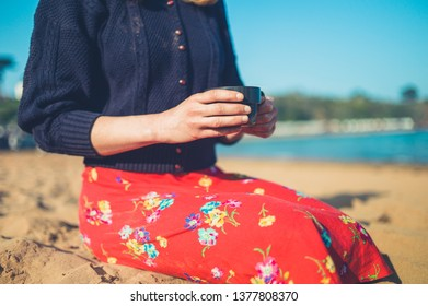 A young woman is drinking coffee on the beach