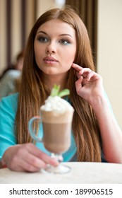 Young woman drinking coffee sitting indoor in urban cafe. Cafe city lifestyle. Casual portrait of teenager girl.