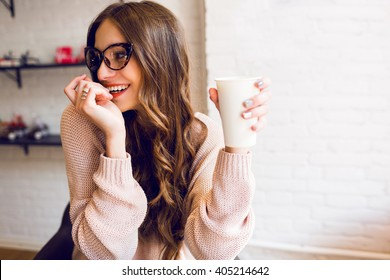 Young woman drinking coffee sitting indoor in urban cafe. Pretty cute  girl  laughing and holding cup of coffee .