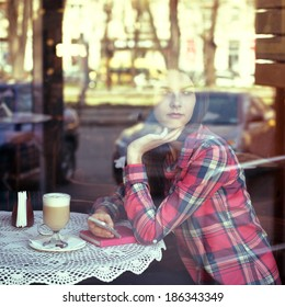 Young woman drinking coffee and use her smartphone sitting indoor in urban cafe. Cafe city lifestyle. Casual portrait of beautiful girl. Toned.