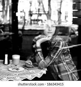 Young woman drinking coffee and use her smartphone sitting indoor in urban cafe. Cafe city lifestyle. Casual portrait of beautiful girl. Black and white